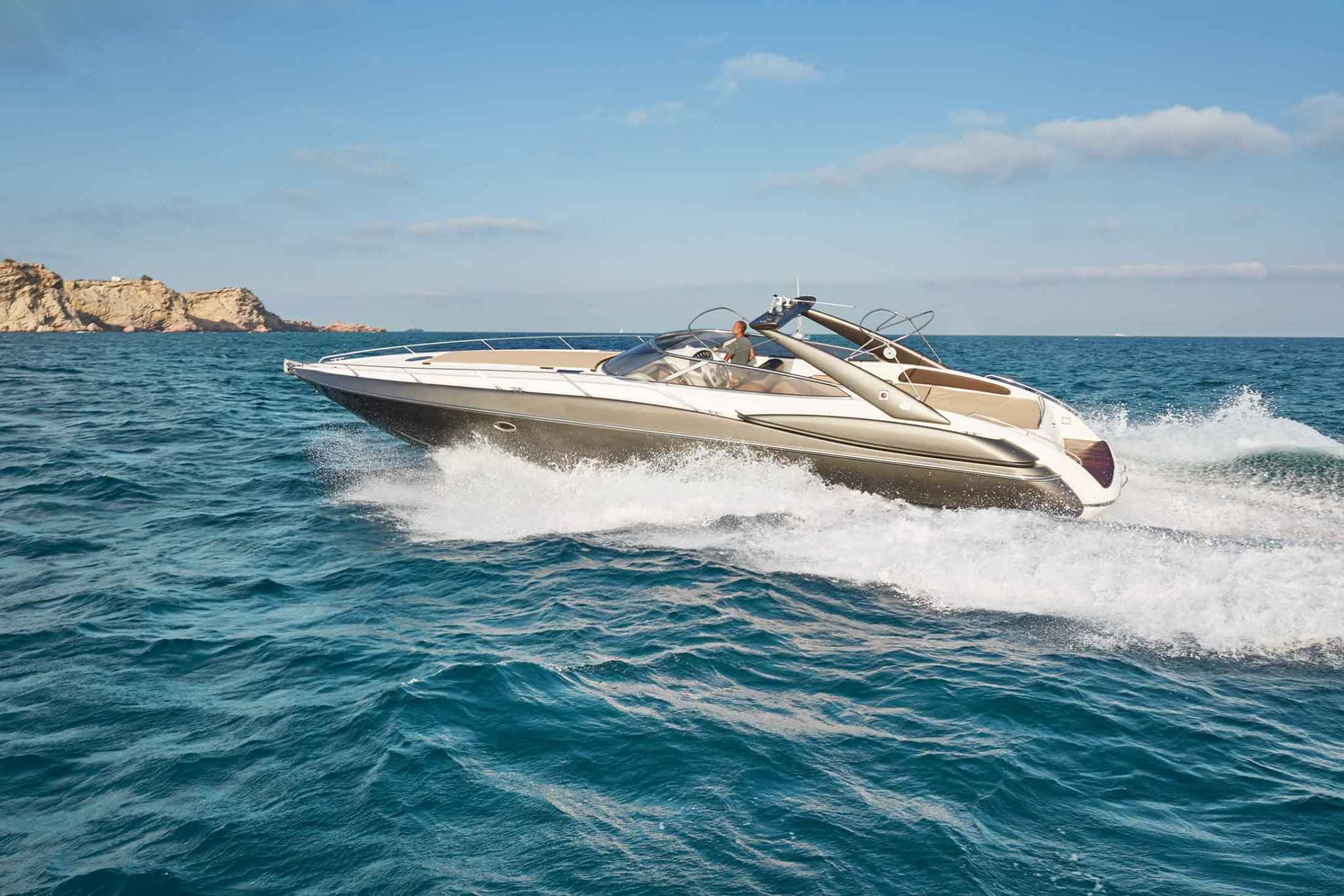 Our charter boat the Sunseeker Superhawk 48 cruising in bright blue water